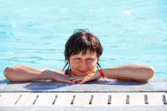 Smiling middle age woman relaxing in swimming pool Stock Image