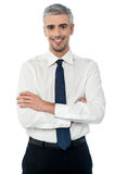 Smiling middle aged business executive. Smiling senior businessman with arms crossed Stock Photo