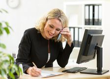 Smiling middle-aged business woman working in Royalty Free Stock Photography