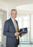 Smiling Middle Aged Businessman with Planner. Smiling middle aged businessman holding a planner notebook. Man is standing in the atrium of a modern office Stock Images