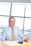 Smiling Middle aged Businessman Seated at Desk Stock Photography