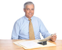 Smiling Middle aged Businessman Seated at Desk Stock Image