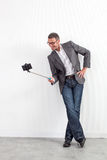 Smiling middle aged businessman taking selfie with stick for fun Stock Photos