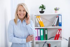 Smiling middle aged businessman talking on the phone in the office. stock photography