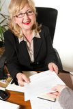 Smiling middle aged businesswoman, with document in her hands. royalty free stock image