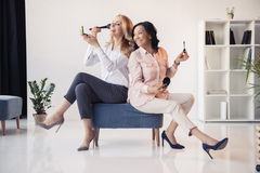Smiling middle aged businesswomen sitting together and applying makeup in office. Two smiling middle aged businesswomen sitting together and applying makeup in Stock Photos