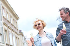 Smiling middle-aged couple holding ice cream cones on sunny day Royalty Free Stock Images