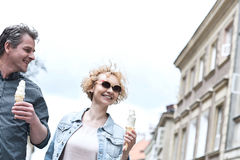 Smiling middle-aged couple holding ice cream cones on sunny day Stock Image
