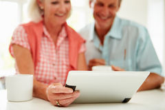 Smiling Middle Aged Couple Looking At Digital Tablet. At Home Smiling royalty free stock image