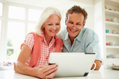 Smiling Middle Aged Couple Looking At Digital Tablet. Sitting At Kitchen Counter Looking Happy Stock Images