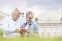 Smiling middle-aged couple reading guidebook outdoors Stock Photography