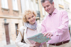 Smiling middle-aged couple reading map in city Stock Image