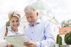Smiling middle-aged couple reading map outdoors Royalty Free Stock Image