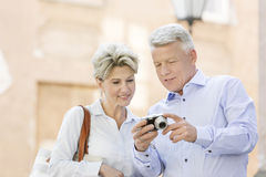 Smiling middle-aged couple reviewing photos on digital camera outdoors Royalty Free Stock Photo