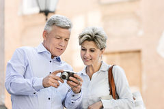 Smiling middle-aged couple reviewing photos on digital camera outdoors Royalty Free Stock Images