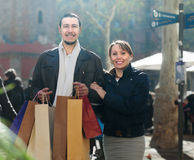 Smiling middle aged couple with shopping bags Stock Image