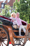 Smiling middle-aged couple sitting in horse cart on city street Royalty Free Stock Photography