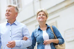Smiling middle-aged couple standing with arm in arm outdoors Royalty Free Stock Photos