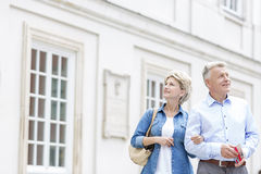 Smiling middle-aged couple standing with arm in arm outside building Royalty Free Stock Photography