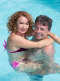 Smiling middle-aged couple in a swimming pool Royalty Free Stock Photos