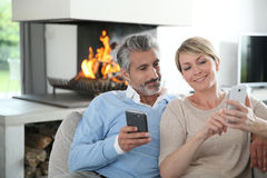 Smiling middle-aged couple using smartphones Stock Photography