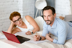 Smiling middle aged couple working on the project at home Stock Photo