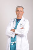 Smiling Middle aged Doctor in Lab Coat. Smiling Middle aged Doctor with his arms folded in Lab Coat and Scrubs, Vertical on a gray background Royalty Free Stock Photos