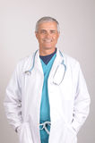Smiling Middle aged Doctor in Lab Coat and Scrubs Royalty Free Stock Photos