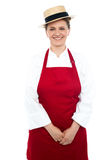 Smiling middle aged female chef wearing hat Stock Photos
