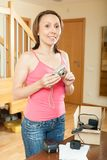Smiling middle-aged girl unpacking new digital camera Royalty Free Stock Image