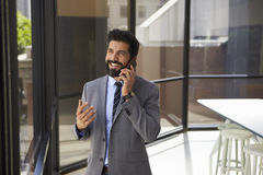 Smiling middle aged Hispanic businessman on phone in office royalty free stock photos