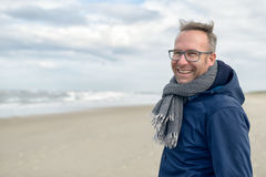 Smiling middle-aged man on an autumn beach. Smiling middle-aged man wearing glasses and a knitted woollen scarf standing on a deserted autumn beach on a cloudy Royalty Free Stock Photo