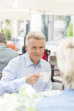 Smiling middle-aged man having coffee with woman at sidewalk cafe Royalty Free Stock Image