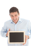 Smiling middle-aged man holding a black board with the blank screen towards the viewer. Smiling middle-aged man holding a tablet-pc with the blank screen towards royalty free stock photos