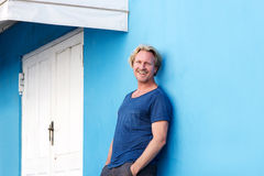 Smiling middle aged man leaning against blue wall Royalty Free Stock Image