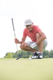 Smiling middle-aged man looking at ball while crouching on golf course Stock Photo