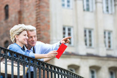 Smiling middle-aged man showing something to woman with guidebook in city. Smiling middle-aged men showing something to women with guidebook in city stock photography