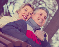 Smiling middle-aged married couple holding hands each other in p. Smiling middle-aged married couple holding hands each other on sunny day in park Royalty Free Stock Photo
