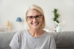 Smiling middle aged mature grey haired woman looking at camera. Happy old lady in glasses posing at home indoor, positive single senior retired female sitting royalty free stock image