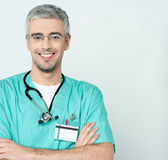Smiling middle aged physician. Handsome smiling experience doctor, arms crossed Royalty Free Stock Images