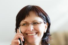 Smiling middle-aged woman call by phone stock images