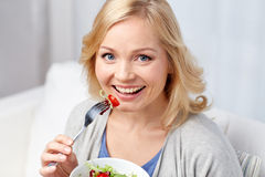 Smiling middle aged woman eating salad at home. Healthy eating, dieting and people concept - smiling young woman eating vegetable salad at home Royalty Free Stock Photography