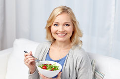 Smiling middle aged woman eating salad at home. Healthy eating, dieting and people concept - smiling young woman eating vegetable salad at home Stock Photos