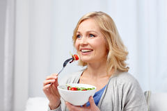 Smiling middle aged woman eating salad at home. Healthy eating, dieting and people concept - smiling young woman eating vegetable salad at home Royalty Free Stock Images