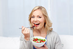 Smiling middle aged woman eating salad at home. Healthy eating, dieting and people concept - smiling young woman eating vegetable salad at home Stock Images