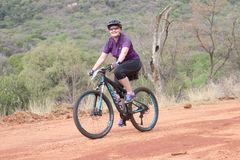 Smiling middle aged woman enjoying outdoors ride at Mountain Bike Race. Rustenburg, South Africa – OCTOBER 23, 2016: Smiling middle aged woman enjoying stock photography