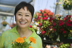 Smiling Middle Aged Woman With Flowers In Plant Nursery Stock Image