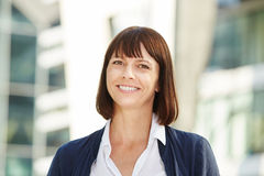 Smiling middle aged woman standing outside Royalty Free Stock Photo