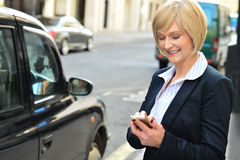 Smiling middle aged woman using cell phone Royalty Free Stock Images