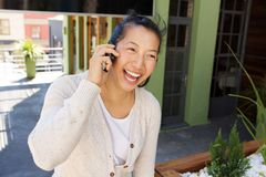 Smiling middle aged woman walking outside and talking on cell phone Royalty Free Stock Photography